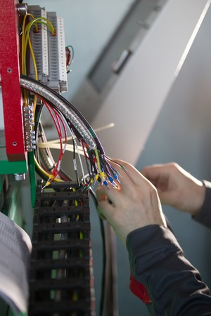 Hands of electrician engineer switching and testing equipment
