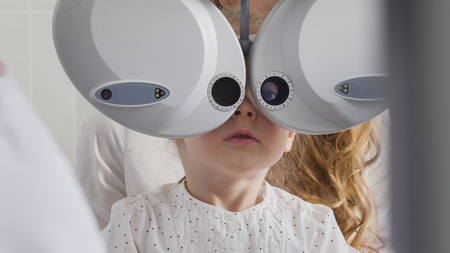 Ophthalmology clinic for children - adorable little blonde girl checks vision eyesight, close up Stock Photo