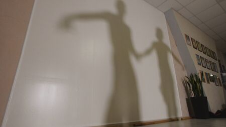Shadow of man and woman dancing and rehearsing Latin American dance in costumes