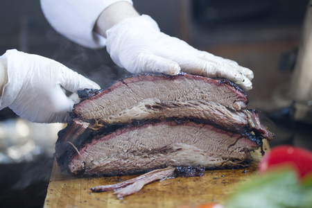 Large piece of smoked meat on a wooden board carved by butcher