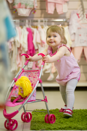 Little cute blue-eyed blonde girl playing in the kids store with the toy baby carriage