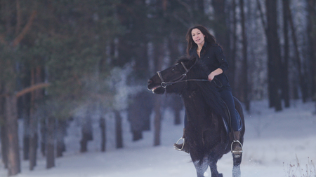 Beautiful longhaired woman riding a black horse through the snow in the forest, stallion prancing