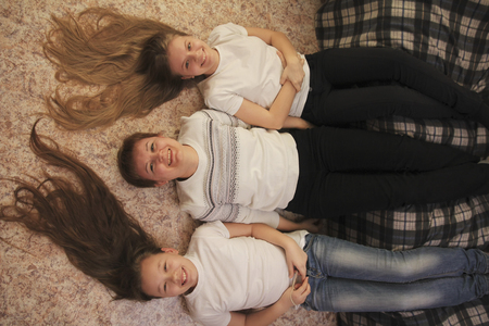 Portrait of young woman and two female teenagers lying on the floor at home, their feet on the couch Banque d'images