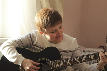 Middle-aged woman playing guitar at home