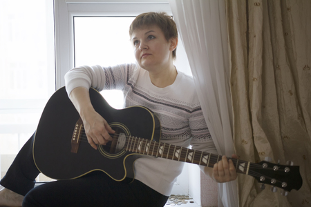 Portrait of dreamy woman with guitar near window at home