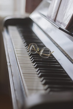 Glasses lying on the keys of a piano