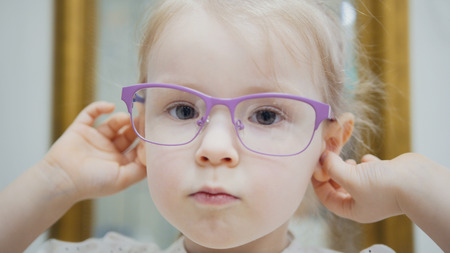 Little girl tries fashion medical glasses near mirror - shopping in ophthalmology clinic Stock Photo