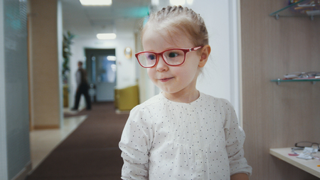Adorable child blonde girl in ophthalmology clinic plays in hall near glasses store