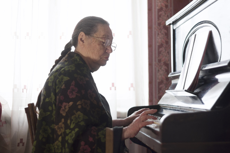 The old lady playing the piano at home Stock Photo