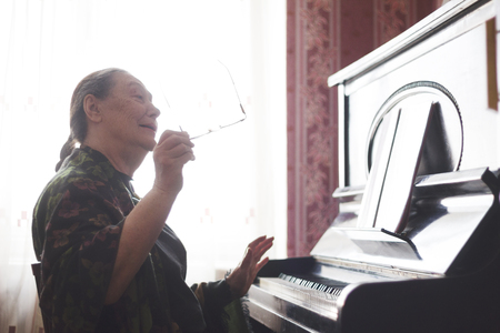 The old lady sitting in front of a piano and singing a song Stock Photo