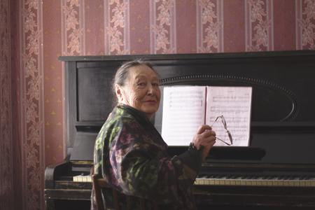 Portrait of old lady sitting in front of a piano with her glasses in her hands
