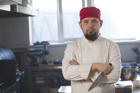 Portrait of a fashionable chef in bandana holding a knife in a kitchen Stock Photo