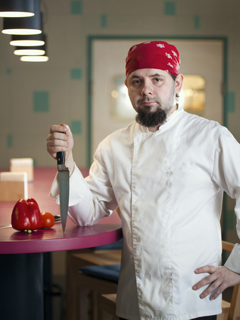 Portrait of a fashionable chef with a knife in bandana Stock Photo
