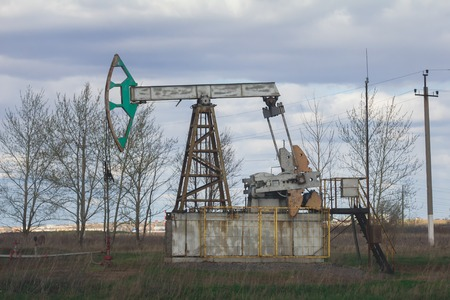 Oil pumpjack among grassy field at sunny day