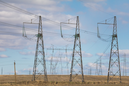 Electricity pylons and lines at summer field, sunny day