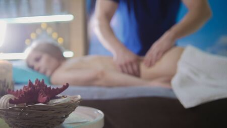 Massage parlor - young girl gets relaxing healing therapy, de-focused Stock Photo