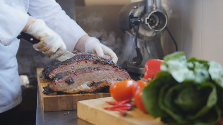 Cutting of a large piece of smoked meat on a wooden board Stock Photo