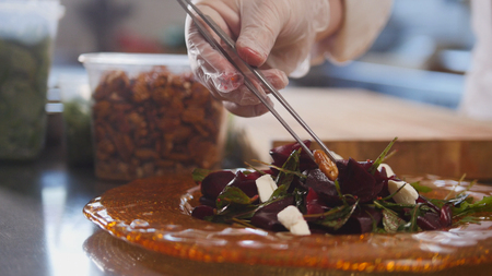 Chef serves the salad by placing the ingredients on a plate and laying the nuts with tweezers