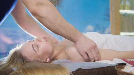 Massage parlor - man doing relaxing therapy for a young blonde woman