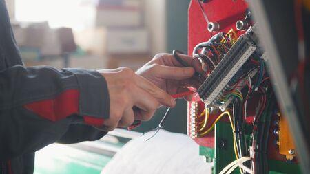 Elektricienshanden die energiesysteem installeren op de machinesindustrie Stockfoto