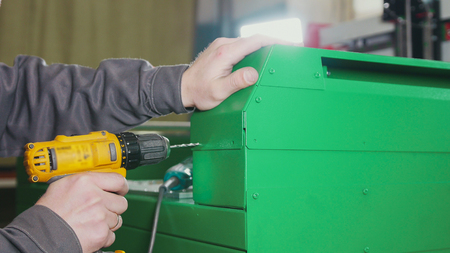 Worker man using an electric hand drill - making hole in green metal machine