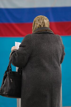 Russian presidential election - old woman puts a ballot paper to voting box Stock Photo