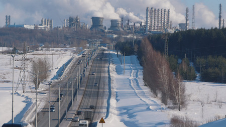 Industrial landscape, winter factory road and smoking pipes Standard-Bild