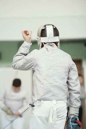 Back of young fencer in white costume and protective mask