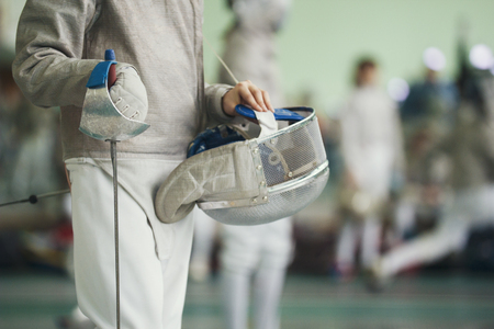 Young fencer holding foil and protective mask in his hand on the fencing tournament Archivio Fotografico