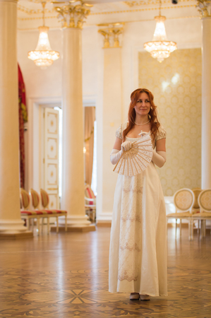 Pretty red haired woman in vintage 18 centuries dresses in ballroom