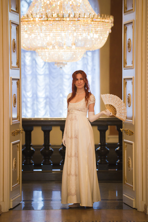 Young red haired woman in vintage 18 centuries dresses use fan in luxury ballroom Stock Photo