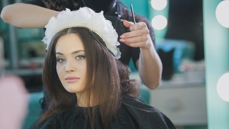 Hairstylist creating a hairstyle for beautyful woman Stock Photo