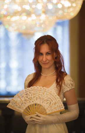Attractive red haired woman in vintage 18 centuries dresses use fan in luxury ballroom Stock Photo