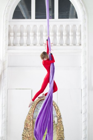 Young attractive woman doing gymnastic elements on aerial silk Stock Photo