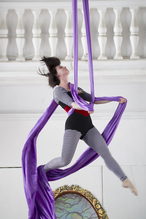 Young woman air gymnast flying on aerial silk