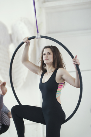 Attractive young woman posing on the aerial hoopin a bright studio