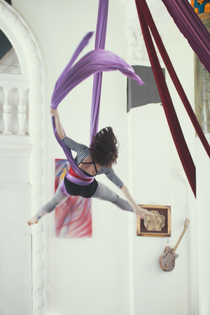 Flexible young woman flying on the aerial silk is a bright studio