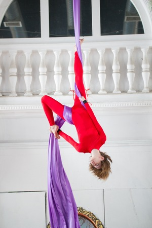 Young attractive air gymnast performs an exercise hanging on aerial silk Stock Photo