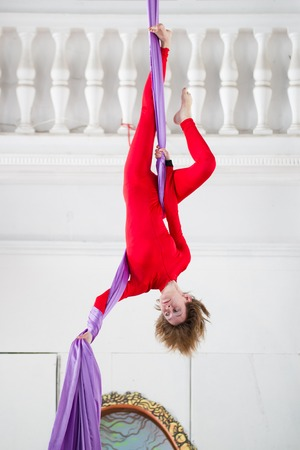 Young attractive woman hangs upside down on the aerial silk Stock Photo