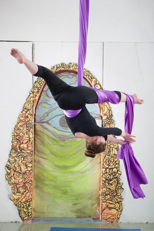 Young smiling aerialist hanging on aerial silk Stock Photo