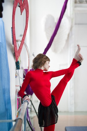 Elegant gymnast doing stretching with barre in a studio