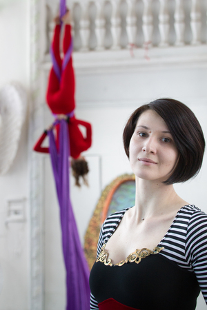 Portrait of young woman in front of air gymnast on aerial silk
