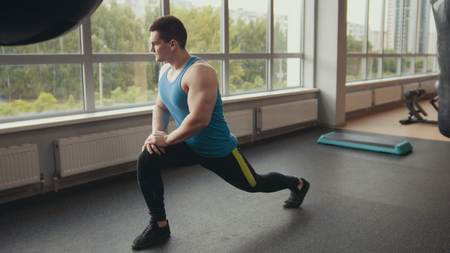 Young muscular man warming up in the gym Stock Photo