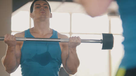 Muscular man in the gym with sports rod in front of mirror