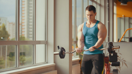 Strong bodybuilder engaged in weightlifting in sunny gym