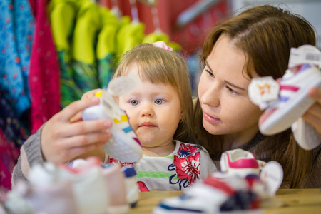 Portrait of little girl with her mother choosing shoes Stock Photo