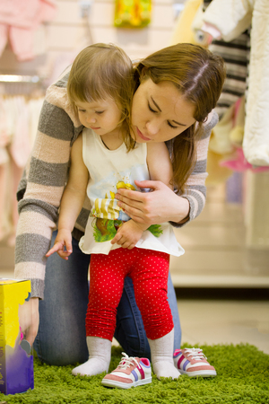 Young attractive mother with her daughter looking at the toy in childrens store