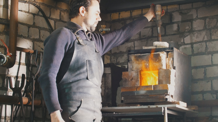 Blacksmith regulates the fire in the furnace with hot metal Banco de Imagens