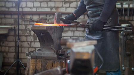 Muscular man blacksmith with hammer in forge creating steel knife