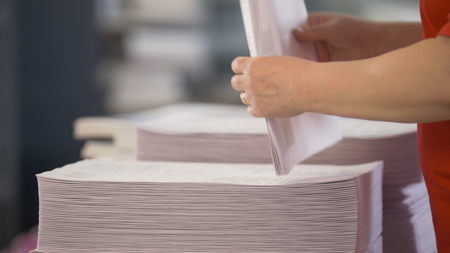 Hands of female workers shift the paper stacks